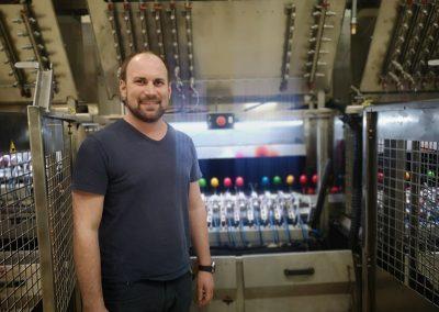 Martin Schrall von seiner Eierfärbemaschine mit Spritztechnik