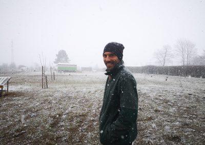 Ferdinand Köberl im Schneefall auf seiner Freilauffläche vor dem Mobilstall
