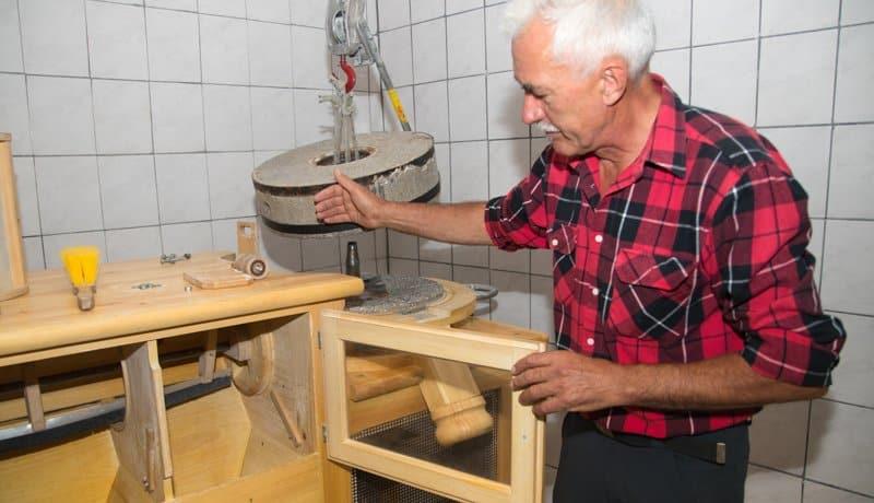 Sepp Brandstätter zeigt die Maismühle mit der er arbeitet