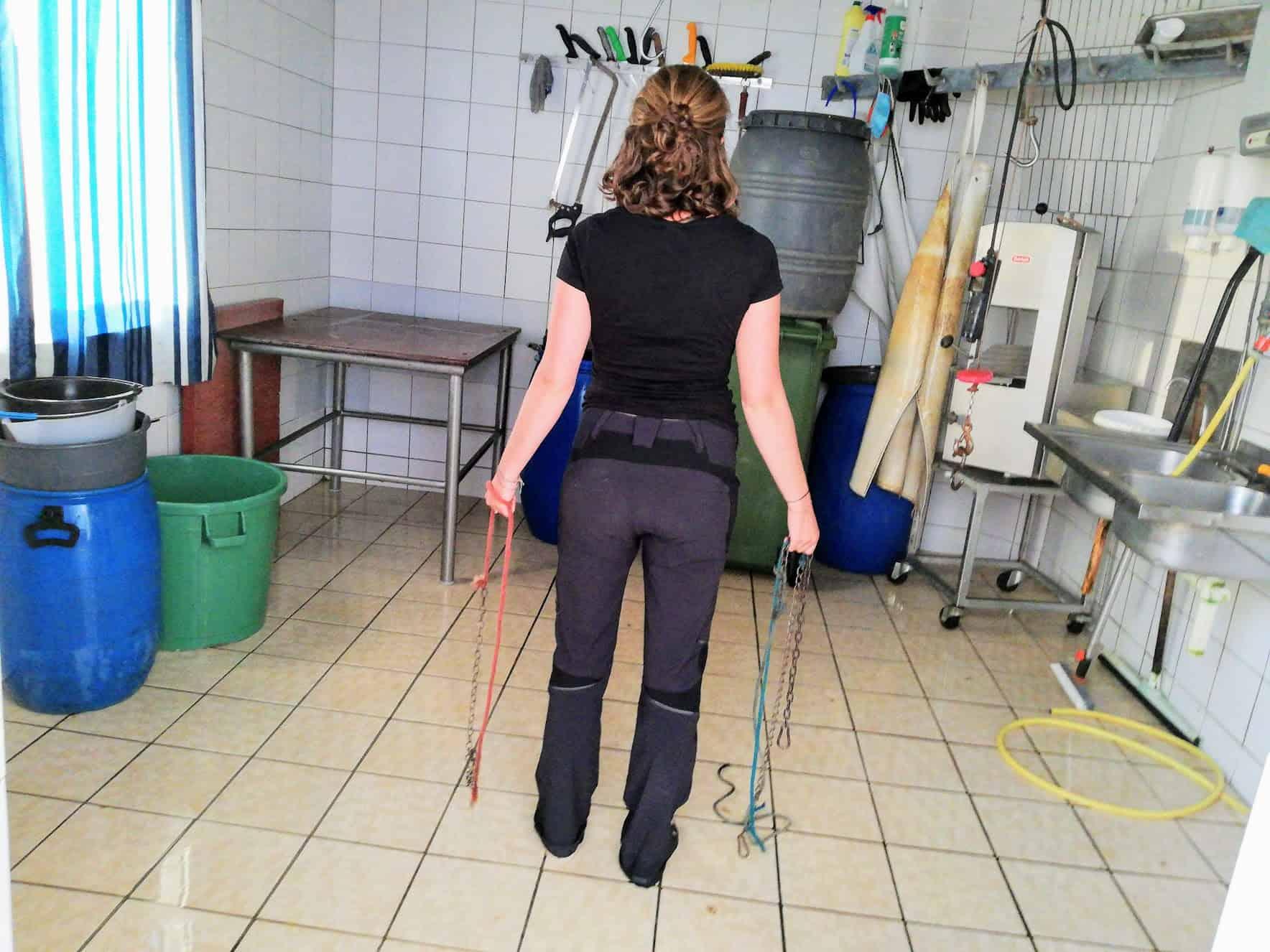 Bianca Blasl von hinten aufgenommen im Schlachtraum mit Ketten in den Händen