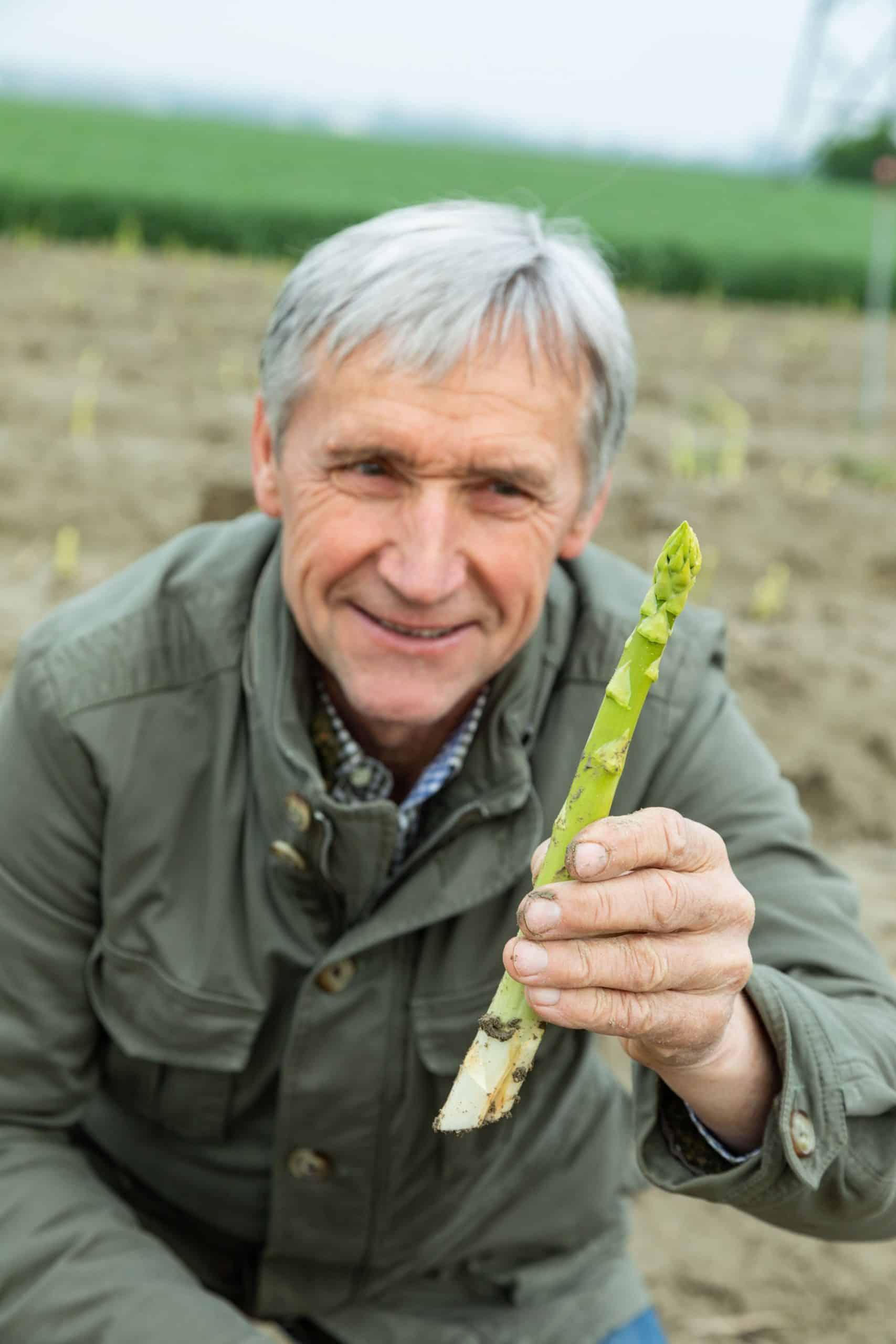 Werner Magoschitz von Sole Select Spargel im Marchfeld kniet mit einem grünen Spargel auf seinem Feld