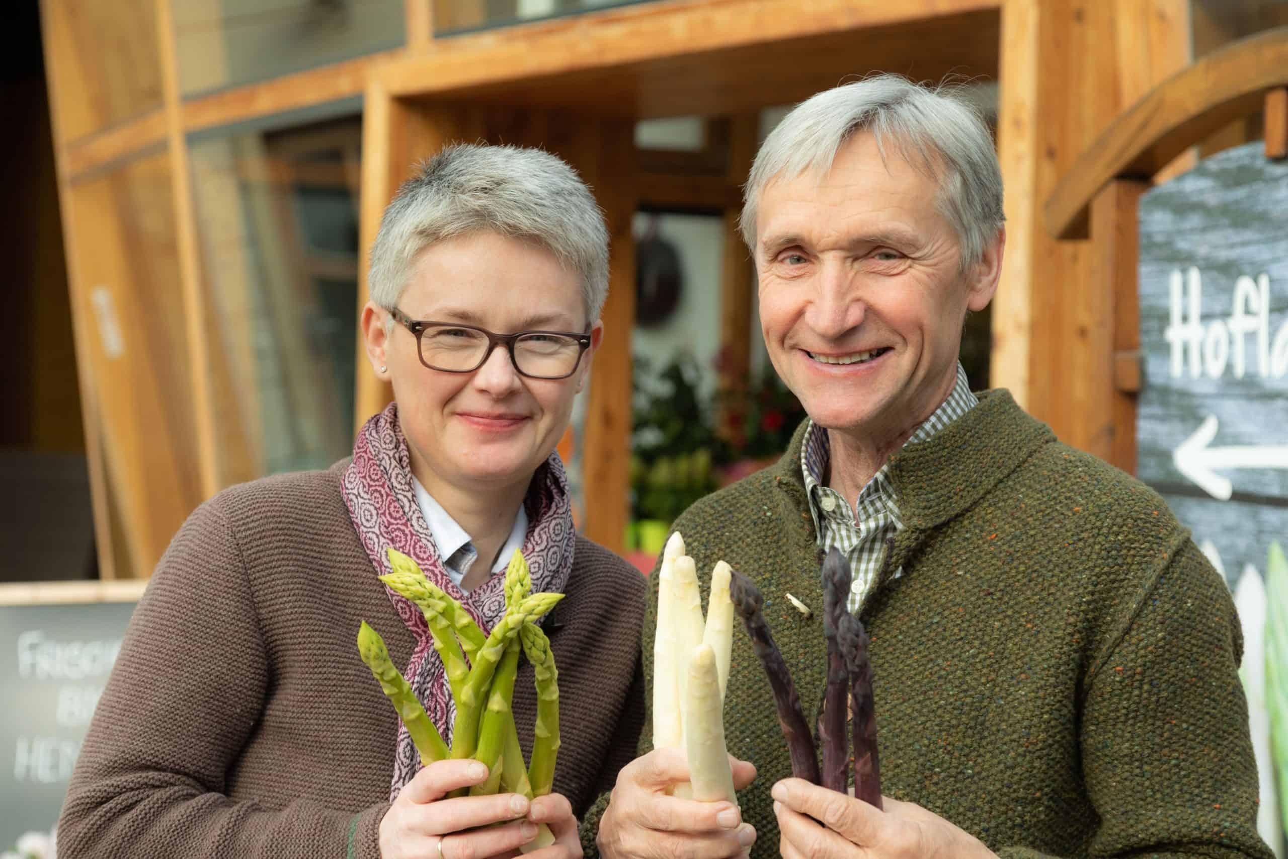Barbara und Werne Magoschitz mit Spargel in den Händen vor ihrem Hofladen